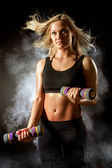 Girl fitness with dumbbells and blue smoke — Stockfoto