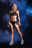 Sexy woman with dumbbells against blue smoke — Stockfoto