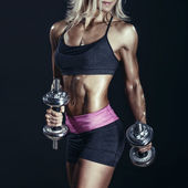 Female bodybuilder in sports clothing ready for gym exercise with dumbbells. — Stock Photo