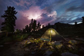 Tent illuminated with light in the night forest with stormy sky — Stock Photo