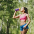 Fitness woman drinking water after running at park — Stock Photo #51549367
