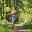 Fitness girl running on forest trail and smiling. beautiful woman runs in park — Stock Photo #51549401