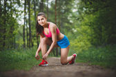 The runner tying her shoelace while training outdoors in the forest — Stock Photo