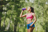 Fitness woman drinking water after running at park — Stock Photo