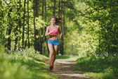 Fitness girl running on forest trail and smiling. beautiful woman runs in park — Stock Photo