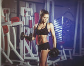 Sexy athlete with a dumbbell in the gym — Stock Photo