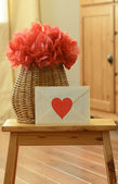 Vase basket with red tissue paper pom pom, and a love letter on the small wooden step stool — Stock Photo
