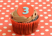 Single frosted chocolate cupcake with number 3 on red polka dots napkin close up — Stock Photo