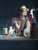 Alchemist girl with test tubes in hand — Stock Photo