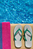 Pair of flip flop thongs and a towel on the side of a swimming pool — Stockfoto