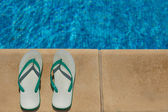 Flip flops on the side of the swimming pool — Стоковое фото