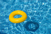 A yellow pool float, pool ring in cool blue refreshing swimming pool — Stock Photo