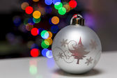 Silver Christmas ball on a reflective table with lights in the background — Stok fotoğraf