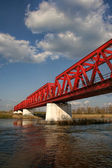 Red metal crossing bridge used by trains to go across a big river — Stockfoto