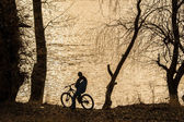 Bike rider on the edge of a river looking at the sunset. Sepia colors — Stock Photo