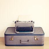 Typewriter and vintage suitcase — Stock Photo