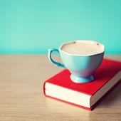 Cup of coffee on book — Stock Photo