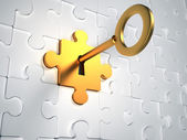 Golden key and puzzle pieces — Stock Photo