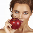 Young beautiful sexy woman with dark curly hair, bare shoulders and neck, holding big red apple to enjoy the taste and are dieting, healthy eating and organic foods, feeling temptation, smile, teeth — Stock Photo #51373883