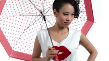 Asian woman with an umbrella posing in studio — Stock Video