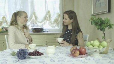 Две привлекательные счастливые молодые женщины с удовольствием на обеденный стол — Стоковое видео