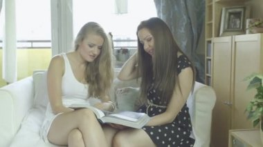 Attractive young girlfriends watching fashion magazine. — Stock Video