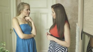 Two beautiful women in colorful dress talking indoor near an old fashion door — Stock Video