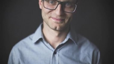 Portrait of young attractive man with glasses smiling  over black background — Stock Video