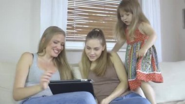 Two women and little girl sitting on couch with tablet computer. — Stock Video