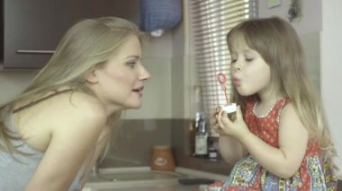 Happy mother and daughter blowing bubbles in the kitchen. — Stock Video