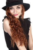 Beautiful girl at age of nineteen in a bkack hat — Stock Photo