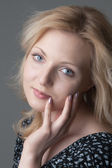 Young beautiful  blonde woman in  black dress with hearts close- — Стоковое фото