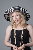 Young beautiful laughing  blonde woman in a hat  and a black dre — Stock Photo
