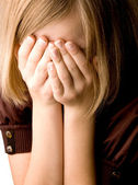 Girl at age of thirteen covers her face with her hands — Stock Photo