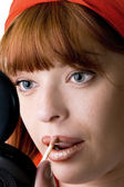 Red haired girl making up — Stock Photo