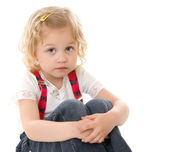 Sad little blond girl in red suspenders — Stock Photo