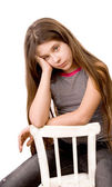 Pretty girl in the age of eleven sitting on white — Stock Photo