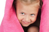 Smiling little girl wrapped in a pink towel — Stock Photo
