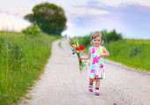Little girl walking on the road with flowers — Stock Photo