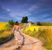 Girl walking the road before sunset — Stockfoto
