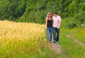 Couple walking in field of wheat — Stock Photo