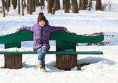 Girl on a bench in winter park — Stock Photo