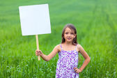 Little girl on neutral background holding sign — Stock Photo