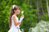 Girl blows away dandelion — Stock Photo