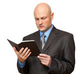Bald man in suit reads a Bible. — Stock Photo