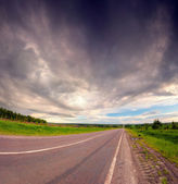Dramatic sky under country asphalt road. — Stock Photo