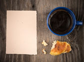 Fresh croissant with coffee and a note paper — Stock Photo