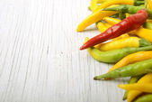 Chili peppers and wood texture — Stock Photo