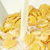 Milk poured on cornflakes — Stock Photo