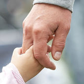 Child and parent holding hands — Stock Photo